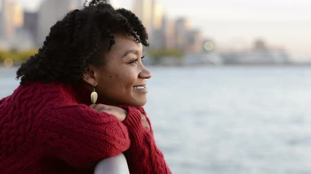 látomás : Close up portrait of a young happy african woman leaning on the banister of a bridge near river. Portrait of happy young african woman at river side thinking about the future. Smiling pensive girl looking across river at sunset and looking at camera.