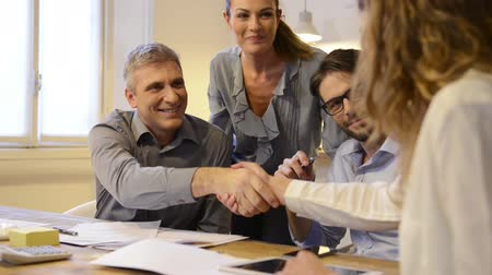 homem de negócios : Handshake to seal a deal after a job recruitment meeting. Two successful businesspeople shaking hands in front of their colleagues. Mature businessman shaking hands to seal a deal with businesswoman in a modern office. Vídeos