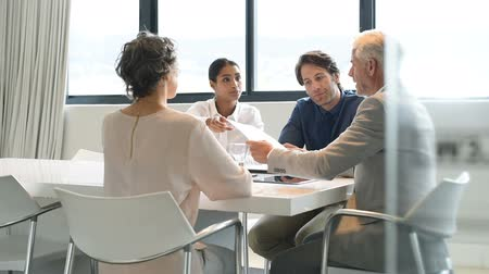 sala de reuniões : Positive multiethnic business people holding a meeting to sum up the results of the year. Group of happy business team during a meeting in a modern board room. Young businesswoman showing a business graph of the company to senior leader in slow motion. Stock Footage