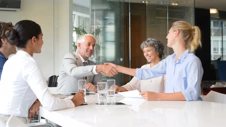 tratar : Business handshake to seal a deal after meeting between young businesswoman, and senior manager. Two successful business people shaking hands in front of their colleagues. Senior businessman shaking hands to his assistance in a modern office in slow motio