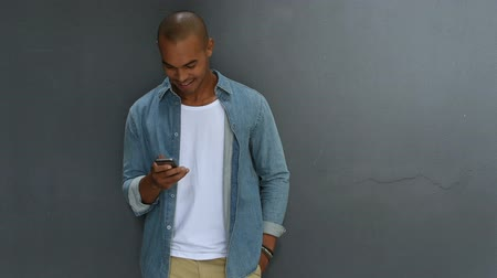 gotículas : Young african man leaning against a grey wall using mobile phone. Portrait of a happy laughing guy texting a phone message. Man in casual typing and reading a message on cell phone with copy space.