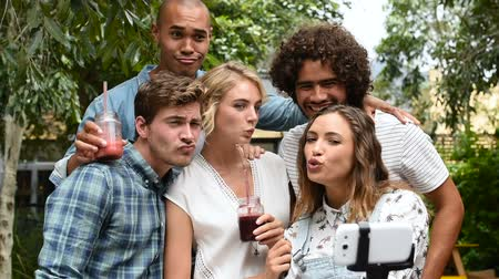 vara : Happy friends with funny face taking a photo with a selfie stick. Group of smiling guys and girls taking picture by smartphone. Happy and cheerful young men and beautiful girls taking a selfie outdoor.
