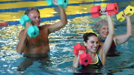 Happy active fitness mature man and senior woman doing exercise with aqua dumbbell in a swimming pool with instructor. Retired people doing aqua gym exercise with water dumbbell in swimming pool. Стоковые видеозаписи