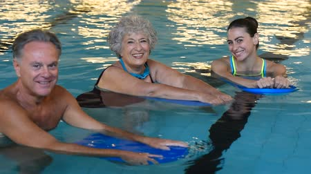 Happy senior couple taking swimming lessons from young trainer. Smiling old woman and mature man doing aqua aerobics exercise in swimming pool. Retired people in swimming pool looking at camera. Dostupné videozáznamy