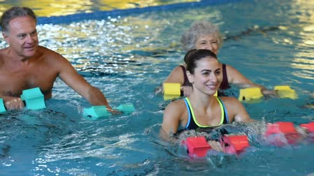 amadurecer : Happy active fitness mature man and senior woman doing exercise with aqua dumbbell in a swimming pool with instructor. Retired people doing aqua gym exercise with water dumbbell in swimming pool and looking at camera.