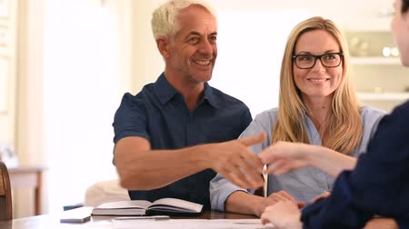 Happy senior couple shaking hands with retirement consultant. Smiling senior man shaking hands with young businesswoman for business agreement. Handshake between senior man and financial agent after obtaining a loan. Стоковые видеозаписи