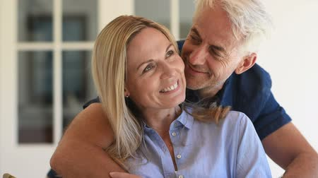 Portrait of a senior smiling couple looking at camera while husband whispering to his wife. Senior man embracing behind his wife and kissing her on check. Happy smiling retired couple in love.