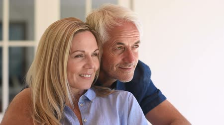 Happy senior couple looking on one side. Smiling mature couple sitting in front of house and looking away. Portrait man embracing his wife and thinking together about the future.