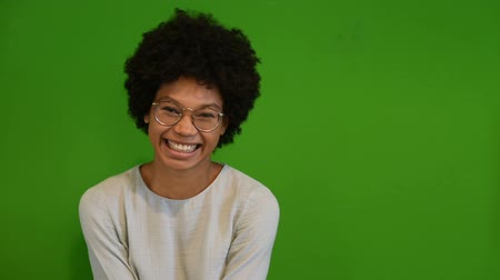 shy girl : Portrait of a happy cheerful young woman looking at camera. Beautiful african girl with curly hair standing against green background. Close up face of black american shy girl isolated on green wall  smiling and looking away.