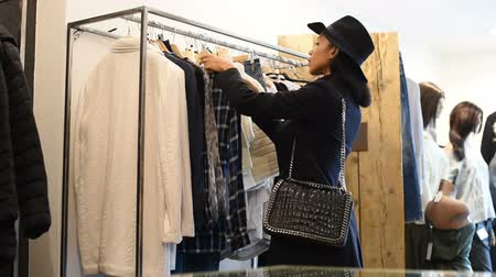 ona : Happy young african woman choosing a black and white blouse from a shop. Young black woman in casuals with black coat and hat checking the quality of blouse she is willing to buy. Happy girl buying and shopping new clothes for wardrobe.