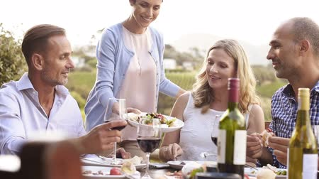 обедающий : Happy smiling woman serving salad to friends and family outdoor in a sunset. Happy mature friends having dinner together. Senior men and middle aged women having fun while eating together at vineyard.