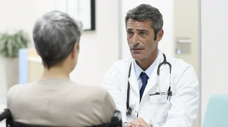 Doctor talking to woman in wheelchair after surgery. Portrait of a mature doctor talking to a senior disabled patient on wheelchair. Confident mature general practitioner in conversation at hospital. Filmati Stock