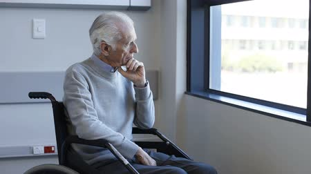 одиноко : Thoughtful senior man sitting on wheelchair at hospital. Sad disabled on wheelchair at the medical center feeling lonely. Retired man alone in a medical clinic.