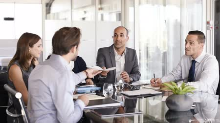 Business man passing over documents to leader during meeting. Businessman passing necessary agreement to the business partner in conference room. Group of businessmen and businesswomen working together.