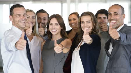 Group of happy business people showing sign of success. Successful business team showing thumbs up sign and looking at camera. Smiling businessmen and businesswomen cheering at office. Стоковые видеозаписи
