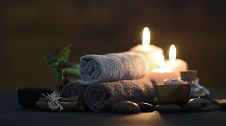 Brown towels with bamboo and candles for relax spa massage and body treatment. Beautiful composition with candles, spa stones and salt on wooden background. Spa and wellness setting with cinnamon and massage oil. Spa and beauty treatment.
