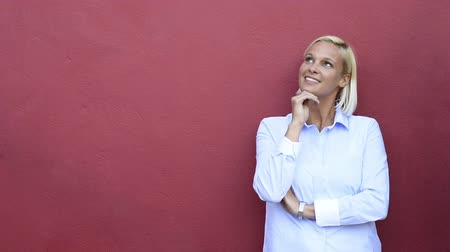 Mid adult woman thinking with finger on chin. Happy pensive mature woman looking up and smiling on red wall with copy space. Portrait of blond thoughtful woman thinking isolated on red background.