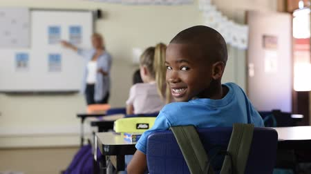 Portrait of african american schoolboy at school desk with classmates in background. Happy young kid sitting and looking behind while teacher teaching in classroom. Portrait of elementary pupil looking at camera.