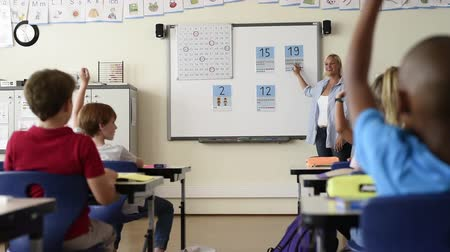 aritmetický : Teacher teaching how to count on whiteboard in the classroom. Woman teaching math to elementary students sitting in class. School children learning mathematics from teacher in modern class room.
