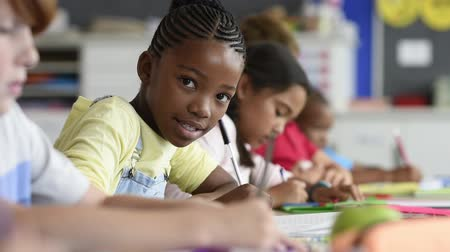 Smiling african girl sitting at desk in class room and looking at camera. Portrait of young black schoolgirl studying with classmates in background. Happy smiling pupil writing on notebook.
