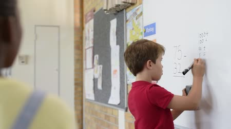 gidermek : Rear view of young boy solving addition and subtraction on white board at school. Schoolboy thinking while solving maths sum. Smart child writing the solution of the mathematical operation in classroom.