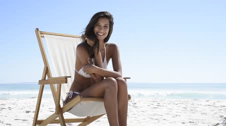 Beautiful woman sitting on a deck chair at the beach and looking at camera. Young tanned woman in white bikini enjoying the summer with copy space. Hispanic woman subathing at seaside and laughing. Relaxed beautiful girl enjoying the sea.