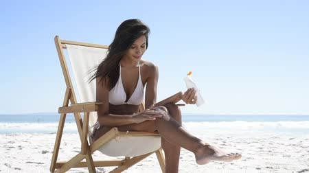 Young latin woman in white bikini applying suntan lotion while sitting on deckchair and looking at camera. Smiling tanned girl applying sunscreen lotion at beach with copy space. Beautiful young woman protect skin from sun.