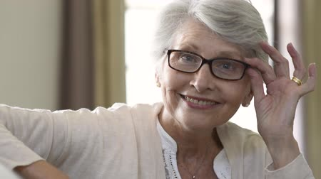пенсионер : Happy retired senior woman looking at camera while holding eyeglasses. Smiling satisfied woman wearing spectacles at home. Closeup face of old grandmother trying on new eyewear. Beautiful elderly woman with eyeglasses smiling at home. Mature woman with gr