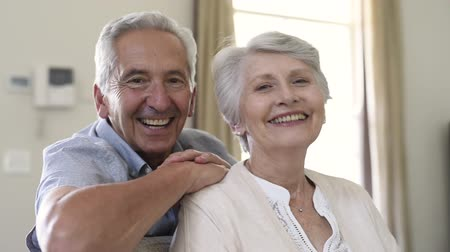 Portrait of happy healthy senior couple at home. Romantic old couple sitting together on sofa while looking at camera. Cheerful elderly wife and husband enjoying life after retirement.