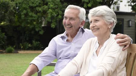 Senior couple sitting together on bench at park. Elderly married couple sitting outdoor and relaxing. Romantic husband embrace his wife while looking away and smiling. Future and retirement concept. Dostupné videozáznamy