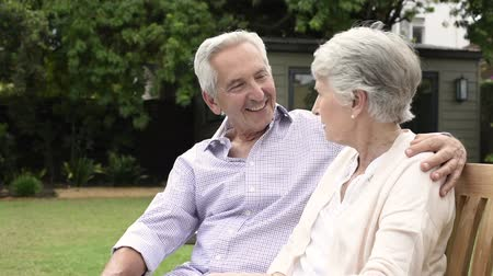 aşk : Senior couple sitting together on bench at park. Elderly married couple sitting outdoor and relaxing. Romantic husband embrace his wife while looking away and smiling. Future and retirement concept. Stok Video