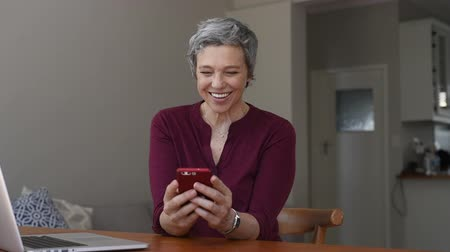 etkileşim : Smiling casual senior woman using laptop while messaging with smartphone. Happy mature woman working with a cellphone and laptop at home and looking at camera. Business woman using her mobile phone. Stok Video