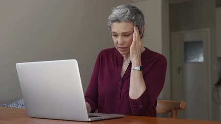 technologia : Mature businesswoman suffering a stress headache sitting at her desk with closed eyes in pain. Senior woman thinking about to complete work task. Depressed tired mature lady suffering from chronic daily headache from computer in a living room. Stressed ol