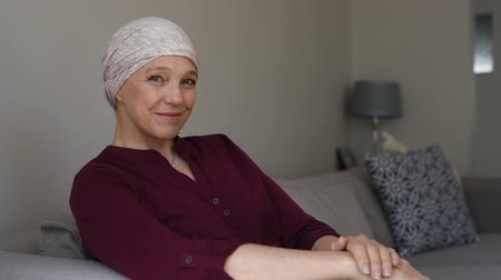 Mature woman with cancer in pink headscarf smiling sitting on couch at home and looking away. Mid woman suffering from cancer sitting after taking chemotherapy sessions looking at camera. Portrait of sad lady facing side-effects of hair loss looking at ca Стоковые видеозаписи