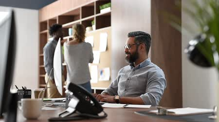Happy middle eastern businessman relaxing in his office while looking computer monitor. Smiling mature business man with beard and eyeglasses sitting with hands behind head at office desk. Relaxed casual man taking a break at workplace. Dostupné videozáznamy