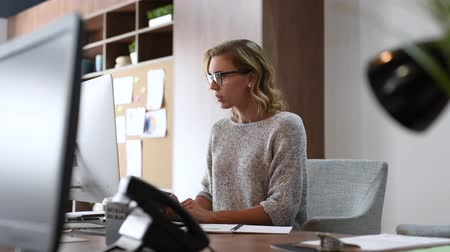 Exhausted businesswoman having a headache in a modern office. Mature creative woman working at office desk with spectacles on head feeling tired. Stressed casual business woman feeling eye pain while overworking on desktop computer.