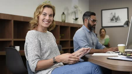 Mature businesswoman using digital tablet during business meeting. Successful mid business woman checking mails and replying from tablet while looking at camera. Portrait of beautiful smiling casual lady working at office meeting with colleagues in backgr