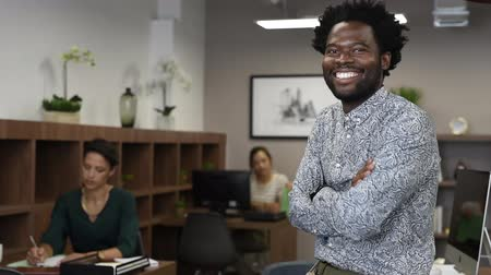 Portrait of happy african businessman looking at camera and sitting at desk. Mature handsome business man in office with colleagues working in background. Successful smiling american man in casual standing with his colleagues at office.