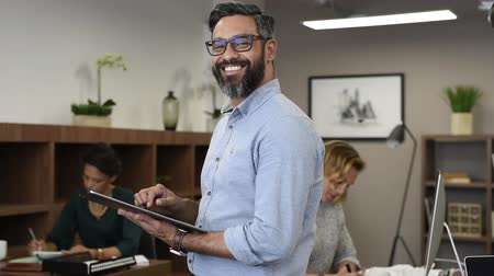 Portrait of happy mature businessman wearing spectacles smiling and looking at camera. Multiethnic satisfied man with beard and eyeglasses feeling confident at office. Successful middle eastern business man using digital tablet with crossed in a creative