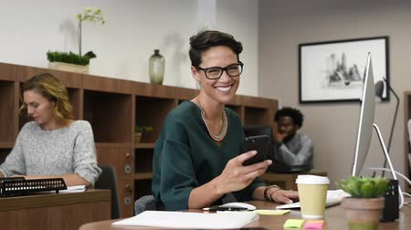 Happy fashionable girl using smartphone while working on desktop computer. Cheerful young business woman sitting in coworking space typing on smart phone and looking at camera. Portrait of beautiful glamour freelancer with eyeglasses working in office whi