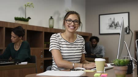Beautiful latin businesswoman looking at camera and smiling while working in office. Cheerful young woman wearing spectacles stitting at desk and holding digital tablet. Creative girl working with colleagues at agency.