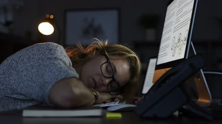 Mature business woman wearing eyeglasses leaning and sleeping on computer keyboard in office. Close up face of tired businesswoman doing overtime sleeping on desktop with screen displaying presentation. Portrait of blonde sleepy woman in dark office. Over