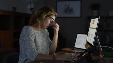 Mature and tired businesswoman working in the office until night in a creative agency. Portrait of a casual stressed lady with headache at desk near the desktop. Exhausted business woman working late night at computer in office. Stress and overwork concep