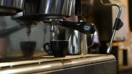 Waiter making coffee at coffee shop. Barman poring coffee from coffee machine. Close up man hands preparing coffee for customer in his small business.