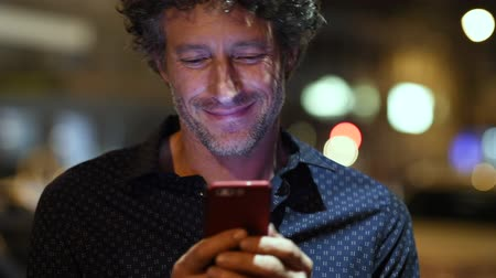 Smiling man using smart phone during night looking at camera. Closeup face of happy mature businessman messaging on cellphone at night on the street with the lights of the road blurred in the background.
