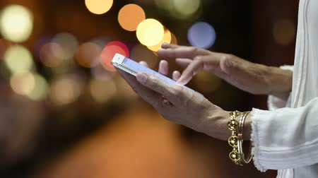 Woman touching smartphone screen at night in city street. Closeup of fashionable woman hands wearing bracelets using mobile phone with light bokeh on street night background. Detail of elegant mature woman typing text message with city nightlife in backgr