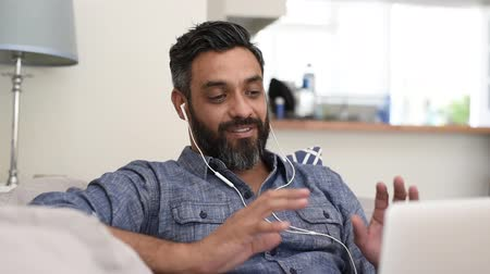 conferencing : Portrait of smiling man video conferencing with laptop. Relaxed mature man video conferencing on computer at home. Happy multiethnic man with beard and spectacles in video call with colleague over through laptop.