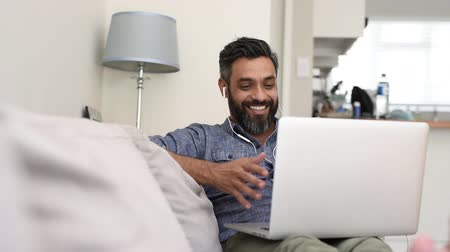 dinleme : Portrait of mature man using laptop with earphones for a video call. Cheerful smiling latin man sitting on couch having a friendly video call. Happy middle eastern man with beard enjoying free wireless internet connection for a discussion while relaxing o