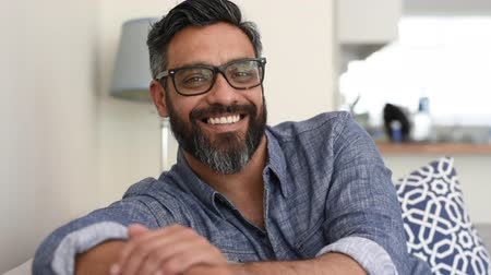 Portrait of smiling man looking at camera sitting on couch. Relaxed middle eastern man sitting on sofa at home. Mature casual man with beard relaxing at home while looking at camwra with eyeglasses.