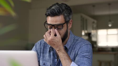 Portrait of an upset latin man working witj laptop. Mature businessman being depressed by working at home with computer. Multiethnic business man feeling strain in eyes after working for long hours on computer.
